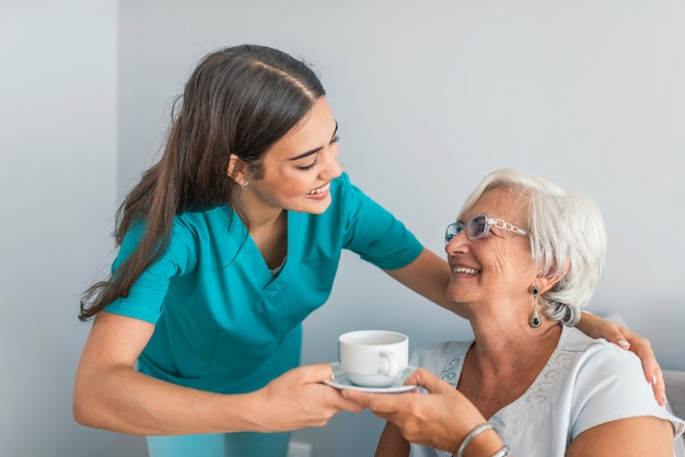 Dwie kobiety, śmiejąc się razem w zabawny żart podczas popołudniowej przerwy na herbatę w domu spokojnej starości
