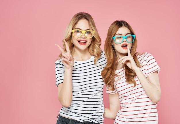 Dwie kobiety stoją obok siebie przytulić przyjaźń lato moda różowe tło