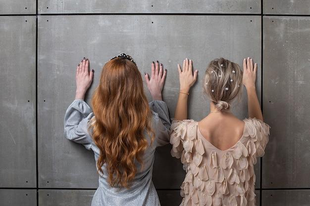 Dwie kobiety stojące przed ścianą