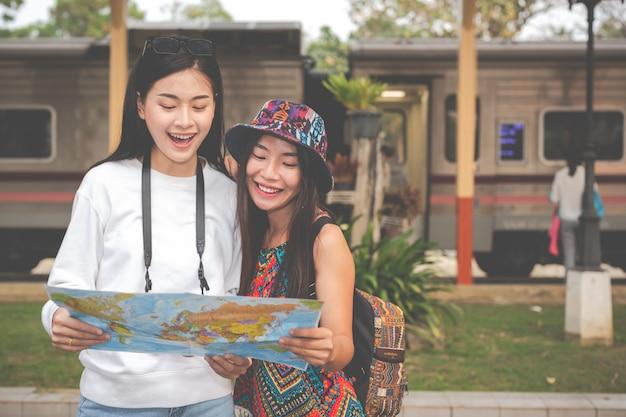 Dwie kobiety trzymają mapę podczas oczekiwania na pociąg. pojęcie turystyki