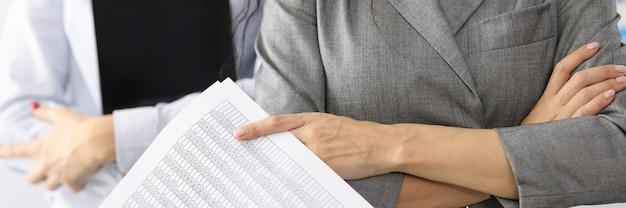 Dwie kobiety trzymają sprawozdanie finansowe i sprawozdanie finansowe tabletu w koncepcji biznesowej