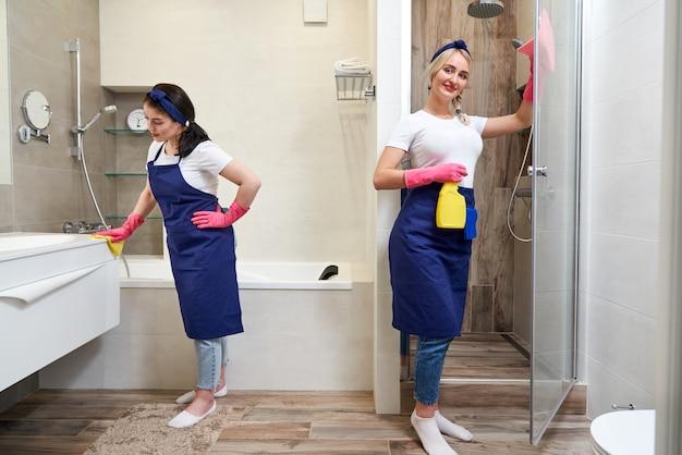 Dwie kobiety ubrane w jednolity stojący w nowoczesnej łazience. koncepcja usługi czyszczenia