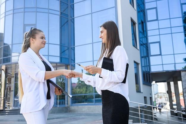 Dwie kobiety uścisk dłoni przed dużym centrum biznesowym business
