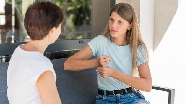 Dwie kobiety używające języka migowego do komunikowania się ze sobą