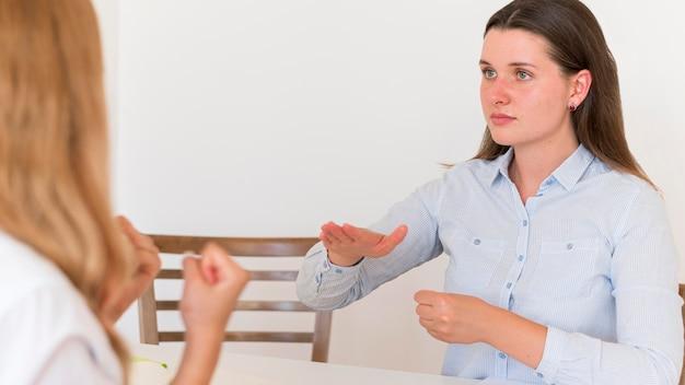 Dwie kobiety używające języka migowego do porozumiewania się przy stole