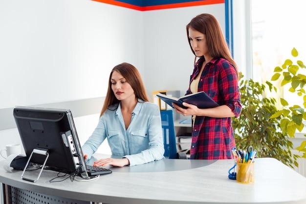 Dwie kobiety w biurze. jedna dziewczyna stoi, a druga siedzi i patrzy na ekran komputera