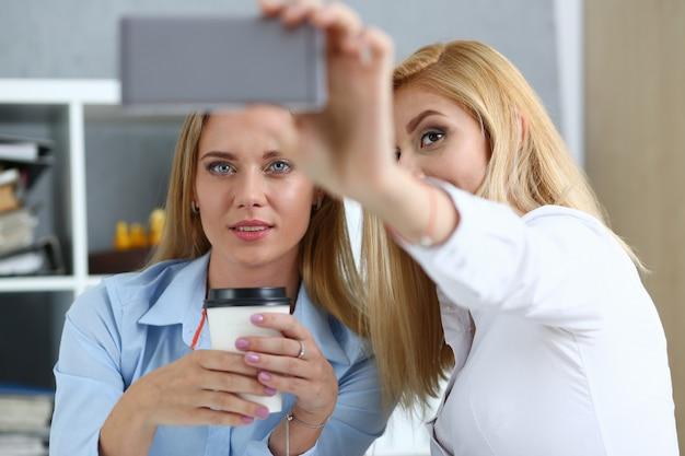 Dwie kobiety w biurze uśmiechają się i robią selfie