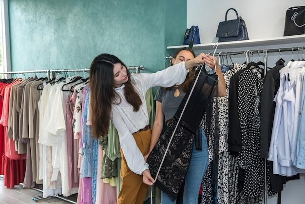 Dwie kobiety w butiku mody wybierają sukienkę. świąteczne rabaty na zakupy. czarny piątek