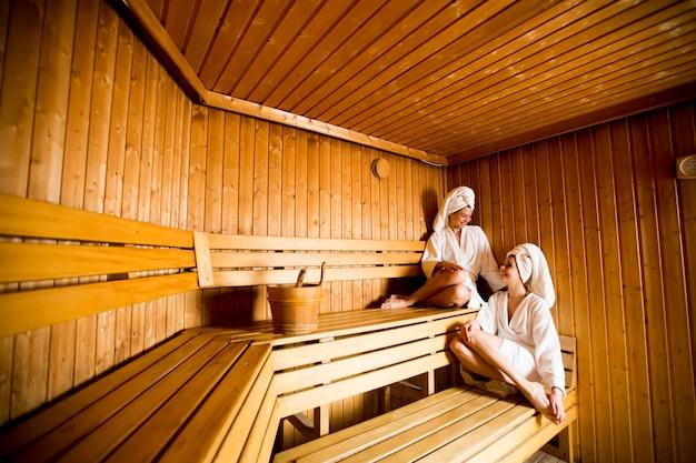 Dwie kobiety w centrum odnowy biologicznej i spa relaks w drewnianej saunie