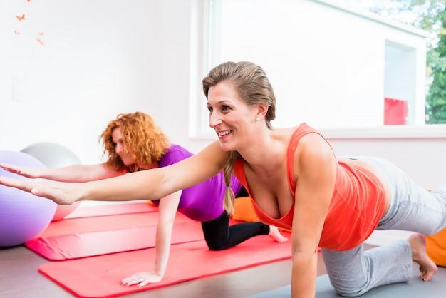 Dwie kobiety w ciąży ćwiczenia podczas zajęć prenatalnych