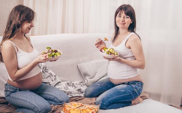 Dwie kobiety w ciąży jedzące pizzę i sałatkę w domu