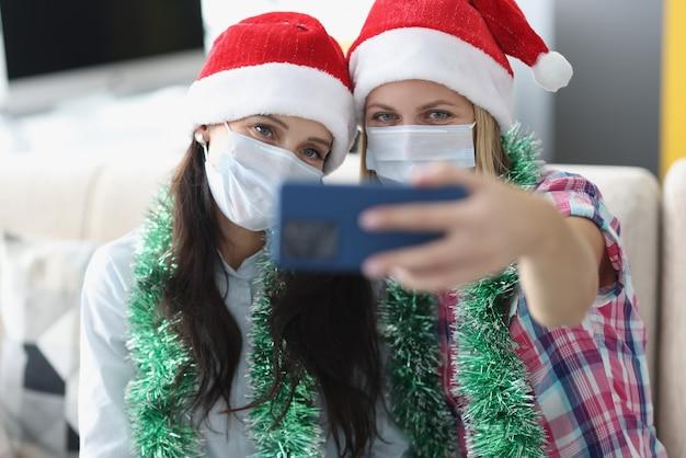Dwie kobiety w czapkach świętego mikołaja i medycznych maskach ochronnych są fotografowane na portrecie aparatu w telefonie