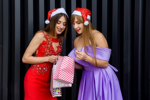 Dwie kobiety w eleganckich sukniach wieczorowych patrzące na prezent. obchody nowego roku
