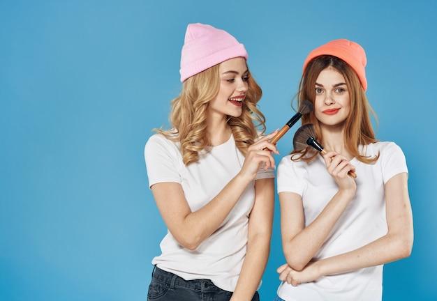 Dwie kobiety w koszulkach kosmetyki przyjaźń niebieska ściana.