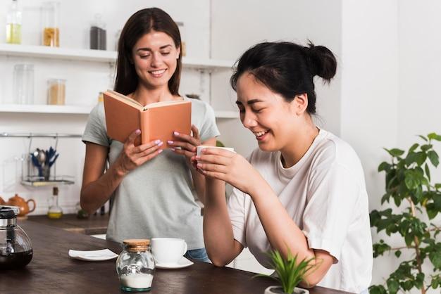 Dwie kobiety w kuchni, czytając i pijąc kawę