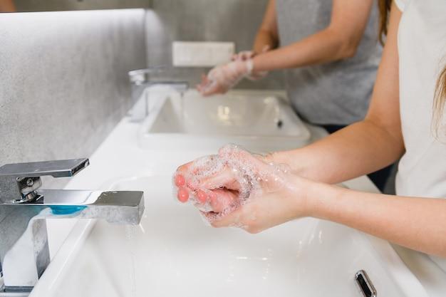 Dwie kobiety w łazience myjące ramiona w pobliżu zlewu i kranu w łazience podczas światowej pandemii koronawirusa, rutyna higieny domowej