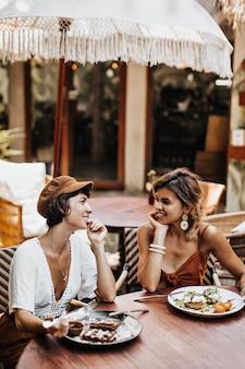Dwie kobiety w letnich stylowych strojach rozmawiają i jedzą pyszne jedzenie w ulicznej kawiarni