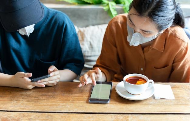 Dwie kobiety w masce ochronnej uniemożliwiają covidowi-19 używanie telefonu komórkowego i picie herbaty cytrynowej w kawiarni.