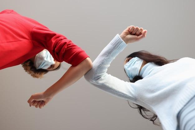 Dwie kobiety w ochronnych maskach medycznych dotykają się łokciami podczas