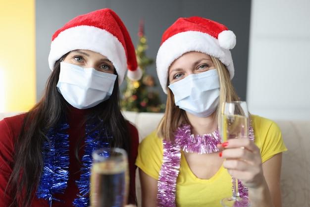 Dwie kobiety w ochronnych maskach medycznych trzymają kieliszki szampana