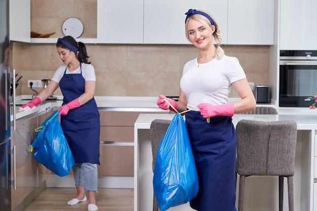Dwie kobiety w ochronnych rękawicach gumowych, trzymając worki na śmieci stojące w kuchni. koncepcja usługi czyszczenia. praca w zespole