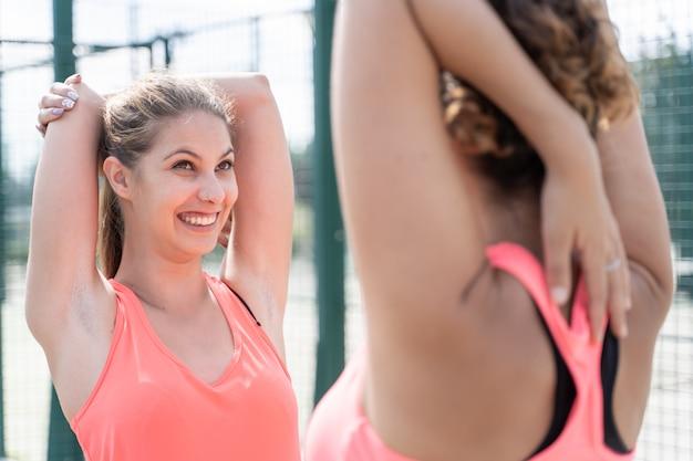 Dwie kobiety w odzieży sportowej wyciągając ręce przed sobą, jednocześnie uśmiechając się