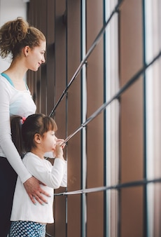 Dwie kobiety w różnym wieku wpatrują się w okno na sali gimnastycznej