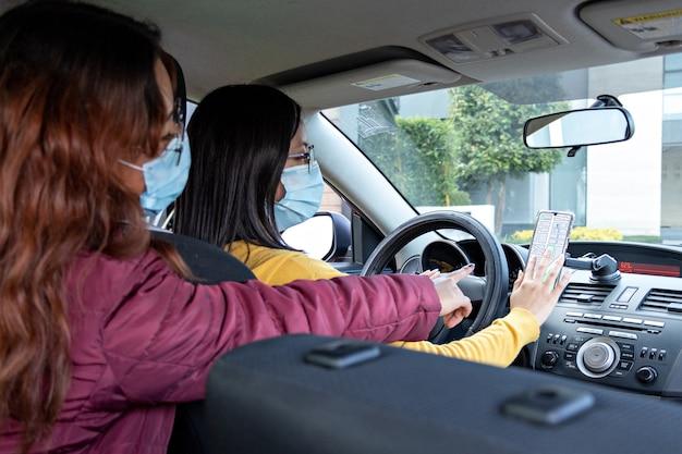 Dwie kobiety w samochodzie noszące maski na twarz, sprawdzające trasę przez telefon komórkowy