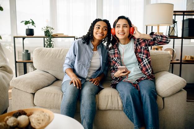 Dwie kobiety w słuchawkach, słuchanie muzyki na kanapie. piękne dziewczyny w słuchawkach odpoczywają w pokoju, miłośnicy dźwięku odpoczywają na kanapie