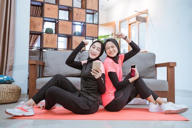 Dwie kobiety w strojach sportowych w hidżabie są szczęśliwe, gdy widzą ekran telefonu komórkowego siedząc na podłodze w domu