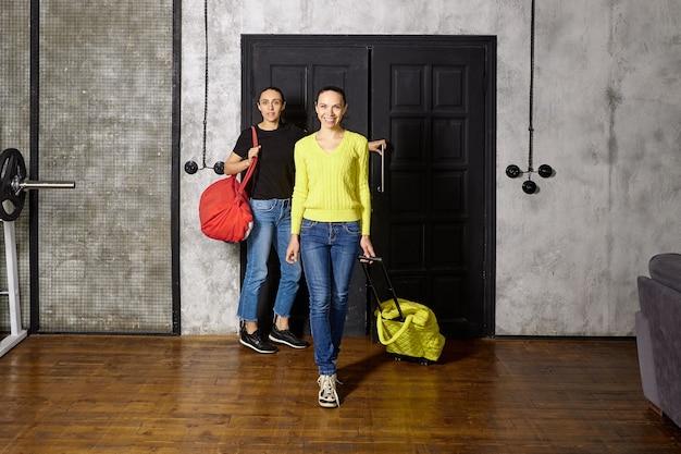 Dwie kobiety wchodzą do mieszkania z torbami podróżnymi