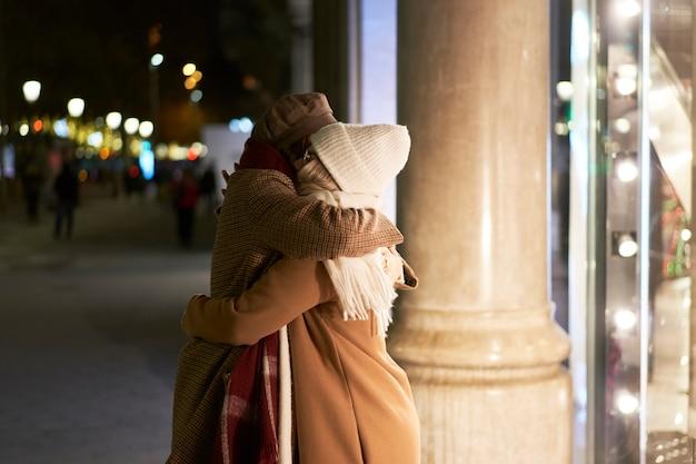Dwie kobiety witają się w uścisku. razem w mieście nocą.