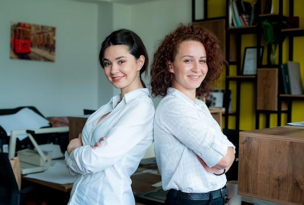Dwie kobiety współpracowników biurowych patrząc na kamery z pewnym uśmiechem na twarzach stojących w biurze