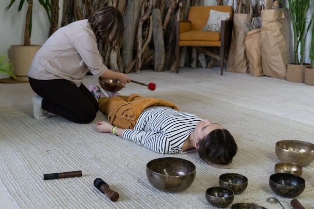 Dwie kobiety wykonują masaż misami tybetańskimi w domu razem ćwiczą tybetańską terapię dźwiękiem do medytacji