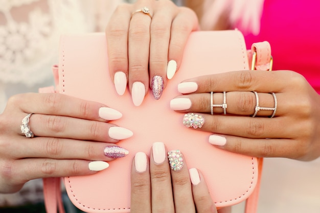 Dwie kobiety z designowym manicure'em trzymające skórzaną różową torbę.