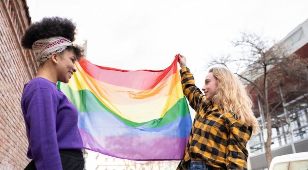 Dwie kobiety z flagą dumy gejowskiej, kobieta afro i inna blondynka, szczęśliwe dwie kobiety z flagą dumy gejowskiej, kobieta afro i inna blondynka, szczęśliwa