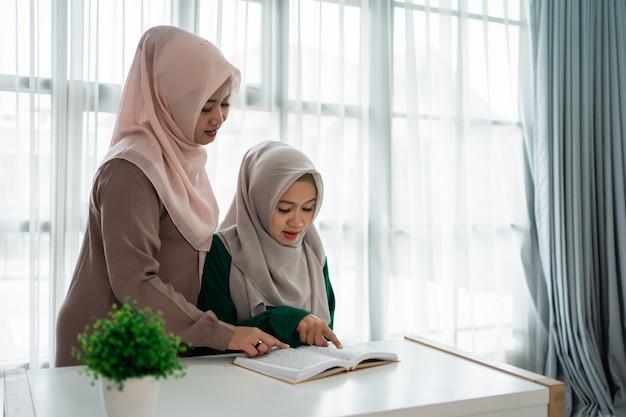 Dwie kobiety z hidżabu studiują i czytają świętą księgę al-koranu