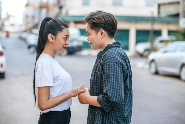 Dwie kochające kobiety stojąc i trzymając się za ręce na ulicy.