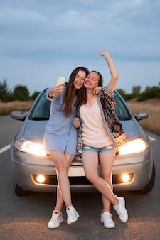 Dwie koleżanki biorąc selfie, opierając się o samochód