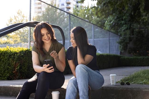 Dwie koleżanki korzystające ze smartfona w parku