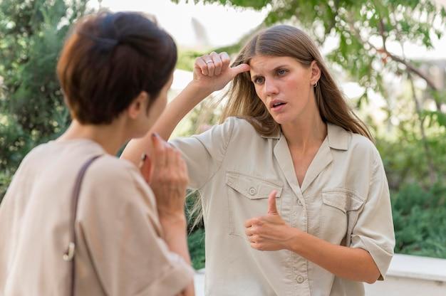 Dwie koleżanki na zewnątrz rozmawiając przy użyciu języka migowego