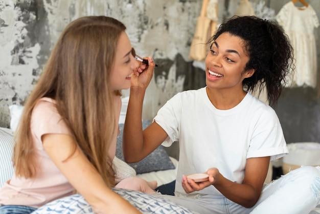 Dwie koleżanki pomagają sobie nawzajem w makijażu