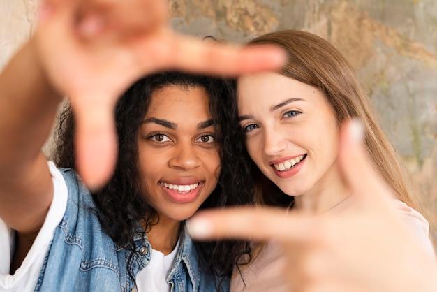 Dwie koleżanki pozowanie podczas tworzenia ramki palcami