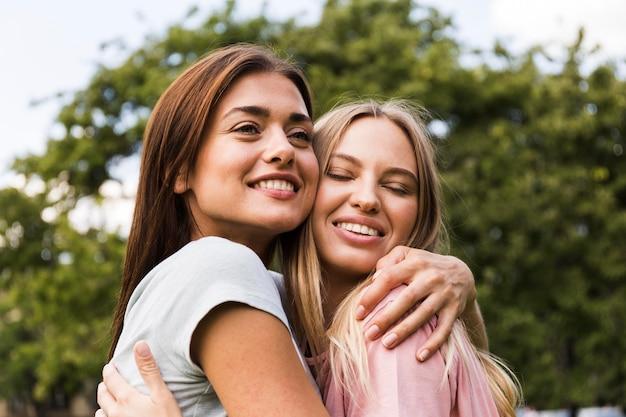 Dwie koleżanki przytulanie siebie na zewnątrz