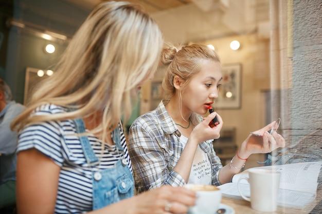 Dwie koleżanki siedząc wewnątrz kawiarni i kawie