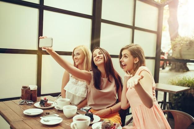 Dwie koleżanki spędzają razem czas, robiąc zdjęcie selfie, pijąc kawę w kawiarni, jedząc śniadanie i deser. młodzież, styl życia, koncepcja komunikacji