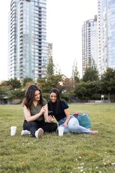 Dwie koleżanki spędzają razem czas w parku i używają smartfona