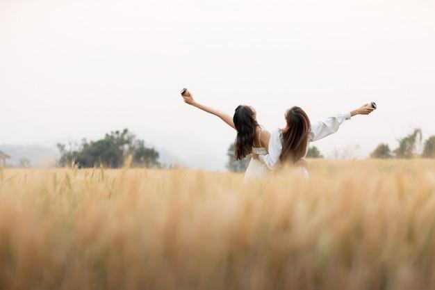 Dwie koleżanki, trzymając filiżankę kawy na wynos i zabawy na polu jęczmienia, rano. szczęśliwy czas.