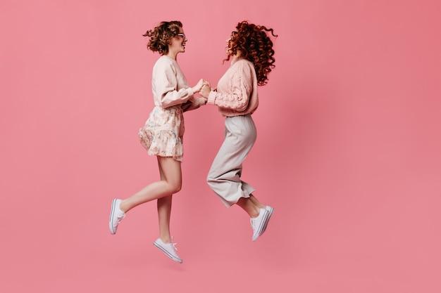 Dwie koleżanki, trzymając się za ręce i patrząc na siebie. widok z boku niesamowitych dziewczyn skaczących na różowym tle.