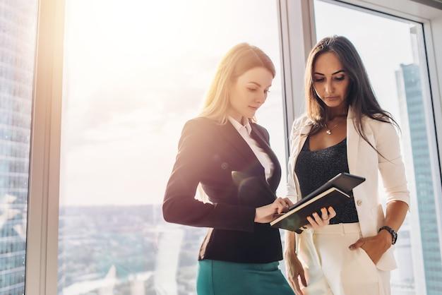 Dwie koleżanki z komputera typu tablet stojąc w budynku biurowym.